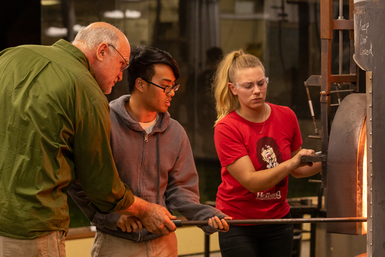 Students working with instructor at glassblowing furnace