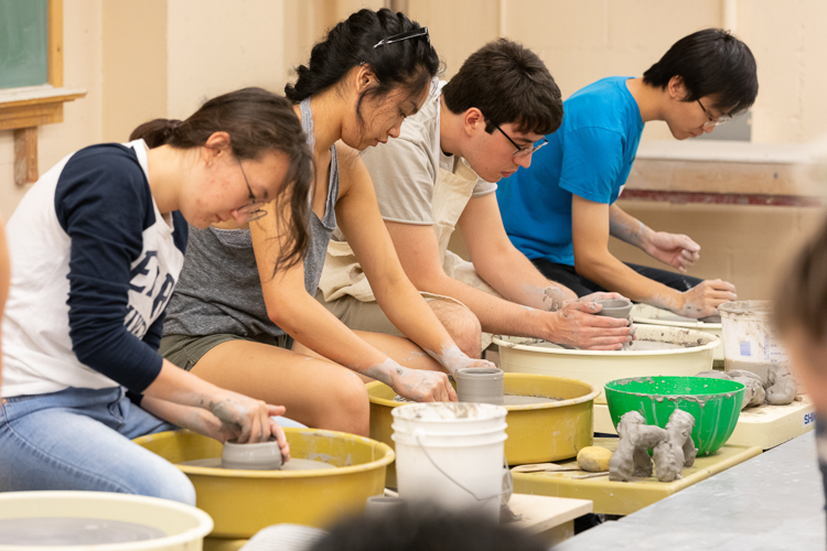 Students creating ceramics/pottery on throwing wheels