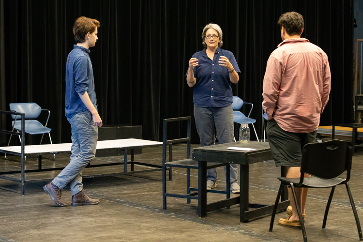 Professor instructing students about acting in studio space