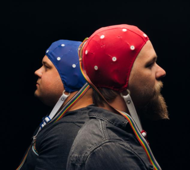 Two people sitting back to back while wearing EEG caps