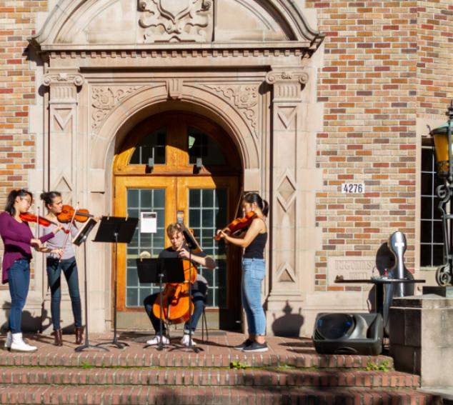 Four students playing stringed instruments in front of a UW building