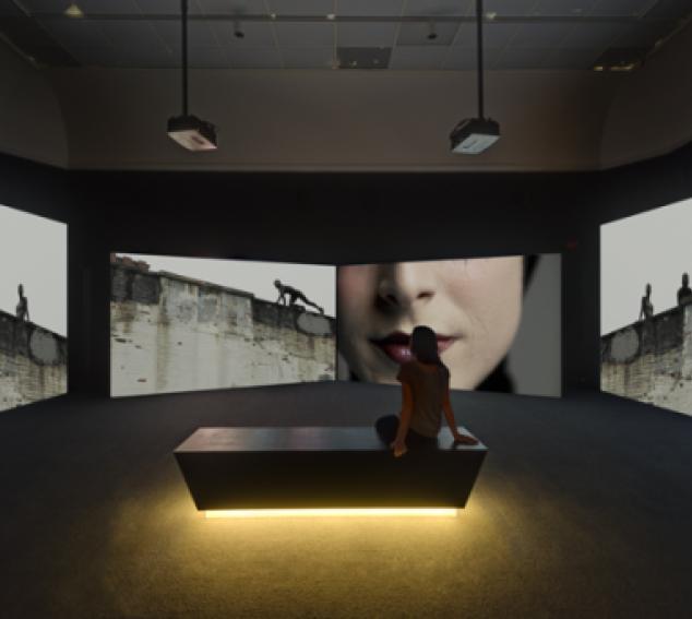 Person sitting in dark gallery space