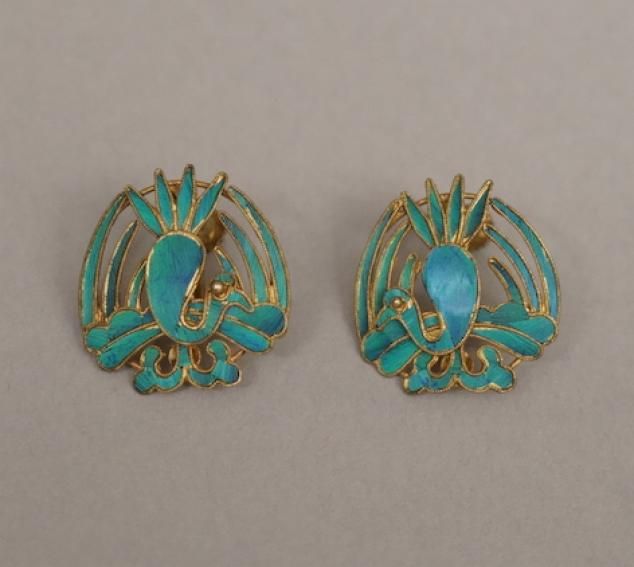 A set of two fabricated golden metal earrings with bright teal blue inlay in the shape of peacocks.